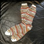 A pair of tiger-striped socks with white toes and embroidered claws.