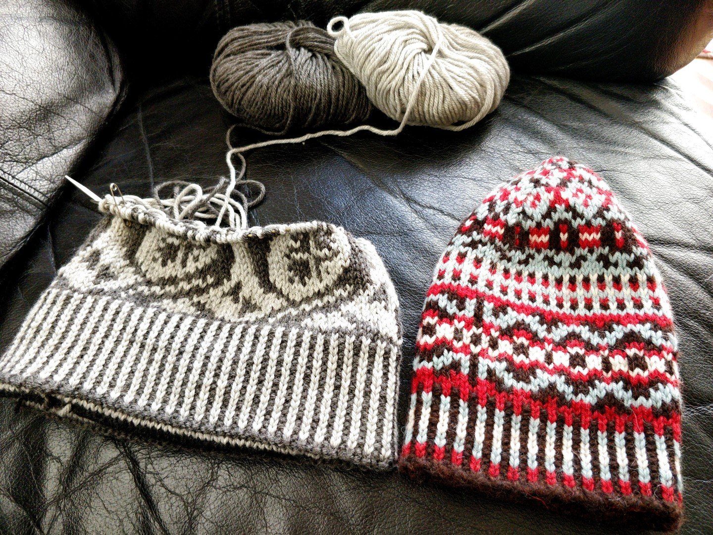 black and white hat WIP next to finished colourwork hat