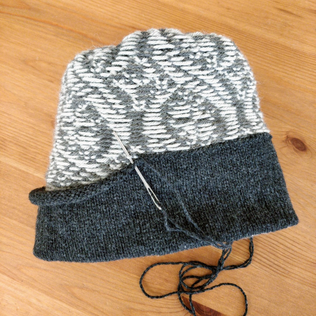 A stranded colourwork hat is inside out, with a facing partially sewn in. A darning needle is halfway into the next stitch to be tacked down.