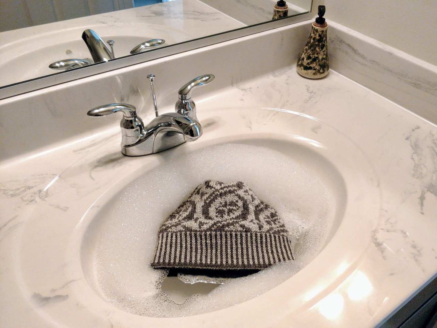 A stranded colourwork hat floats in a bathroom sink full of water topped with bubbles.