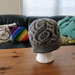 A colourwork hat in dark and light gray sits on a styrofoam head on a coffee table.