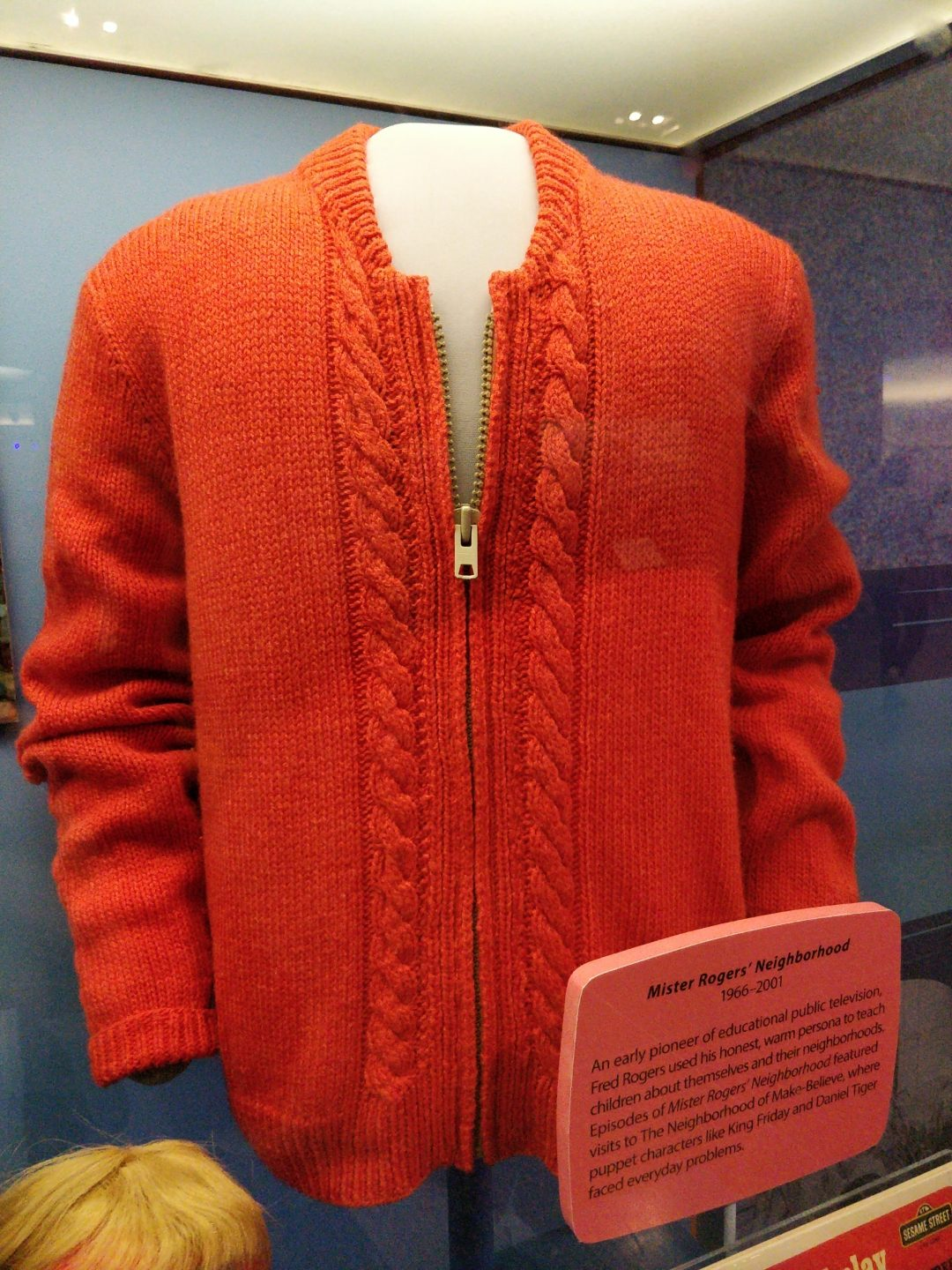 Mr. Rogers's red cardigan sweater with cables on either side of the zipper
