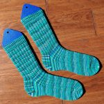 A pair of ribbed socks in a variegated teal colourway.
