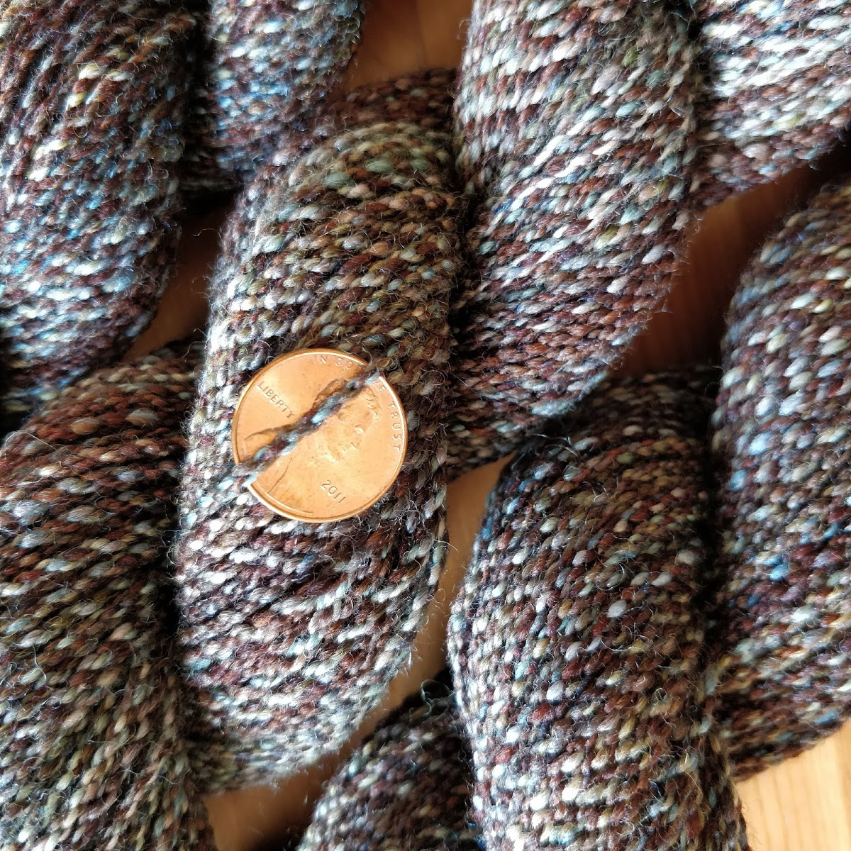 Closeup of cabled yarn with a penny for scale. It is a little thicker than sock yarn and has a bumpy texture.