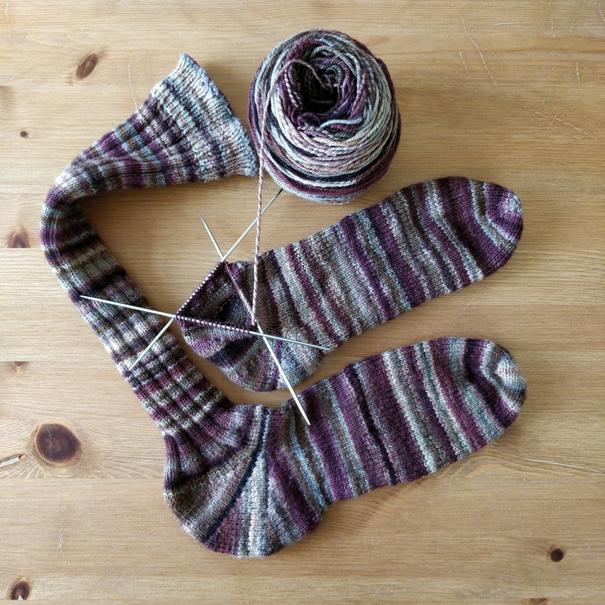 One and a half knee socks in burgundy stripes, and half a ball of yarn.