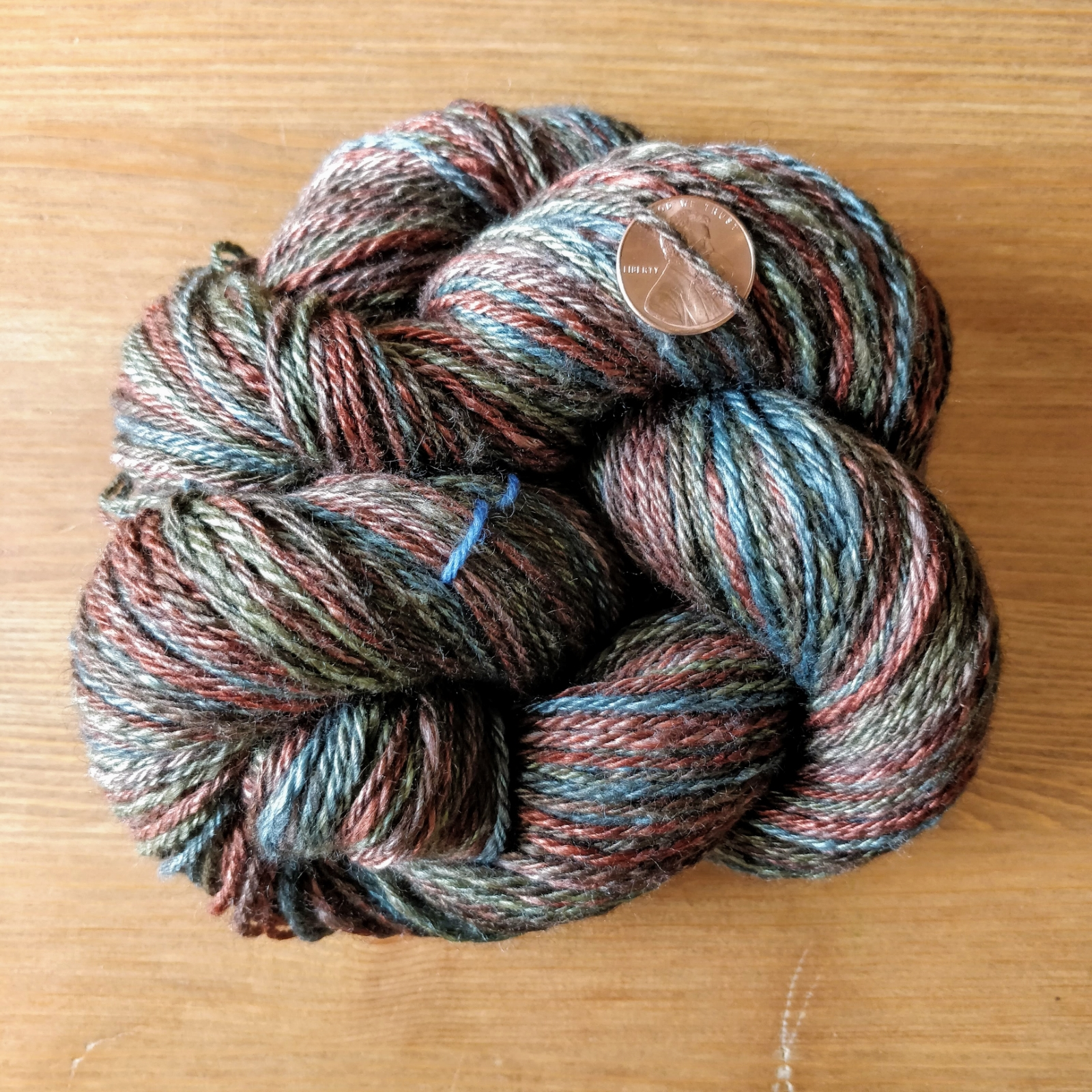 skein of fingering-weight yak-silk yarn in reds, browns, greens and blues