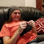 Michael knits while wearing his new floppy hat.