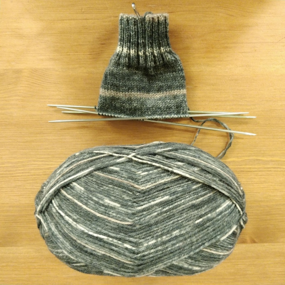 The very beginning of a subtly striped green sock on the needles, with a mostly unknit ball of yarn.