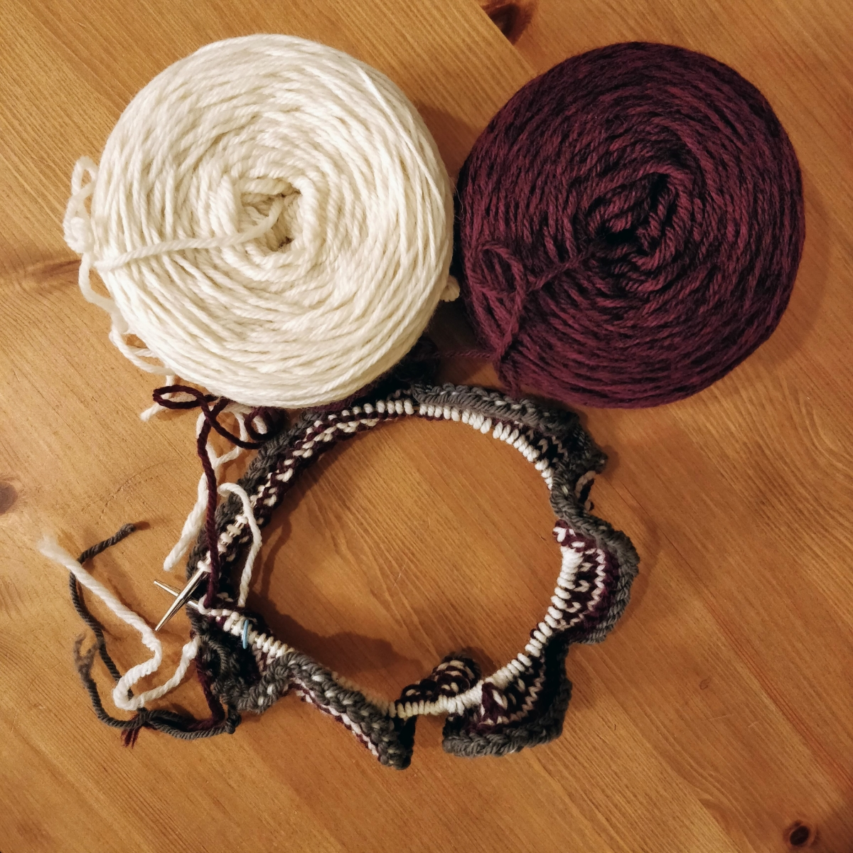 Burgundy and white balls of yarn, with a circular needle that has the beginnings of a new hat.