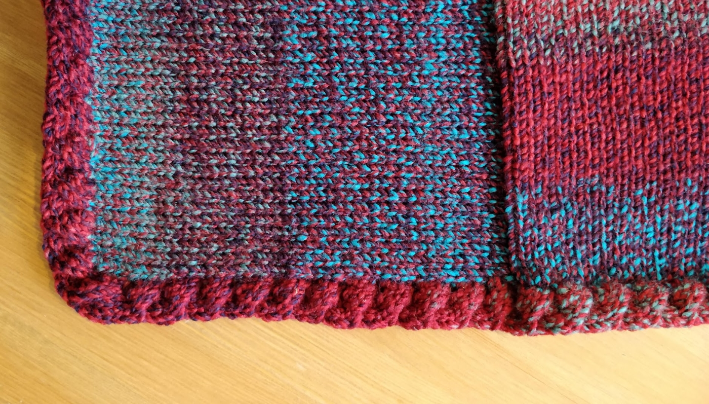 The corner of a blanket square swatch showing a cabled edging.