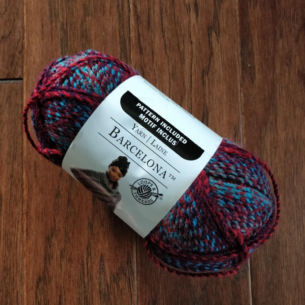 "A large ball of red and teal ""Barcelona"" yarn. The brand is Loops and Threads."