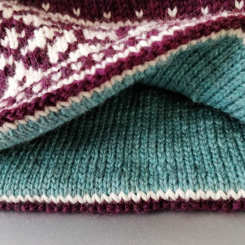 A blue lining peeks out from inside a red and white fair isle hat.