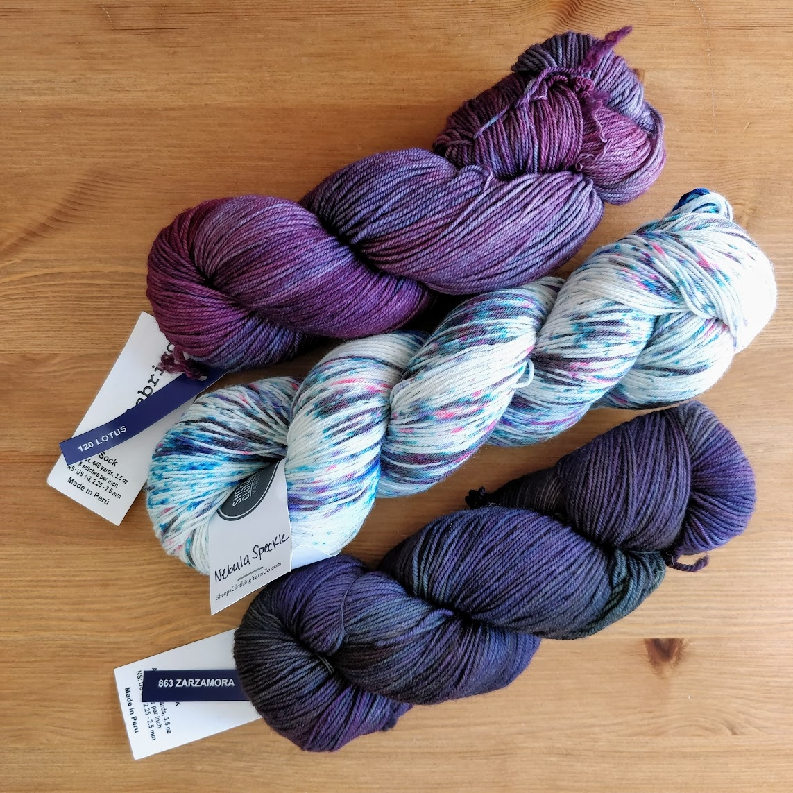 Two skeins of sock yarn in rosy-purple and blue-violet with a skein of purple, pink, and blue speckled yarn between them.