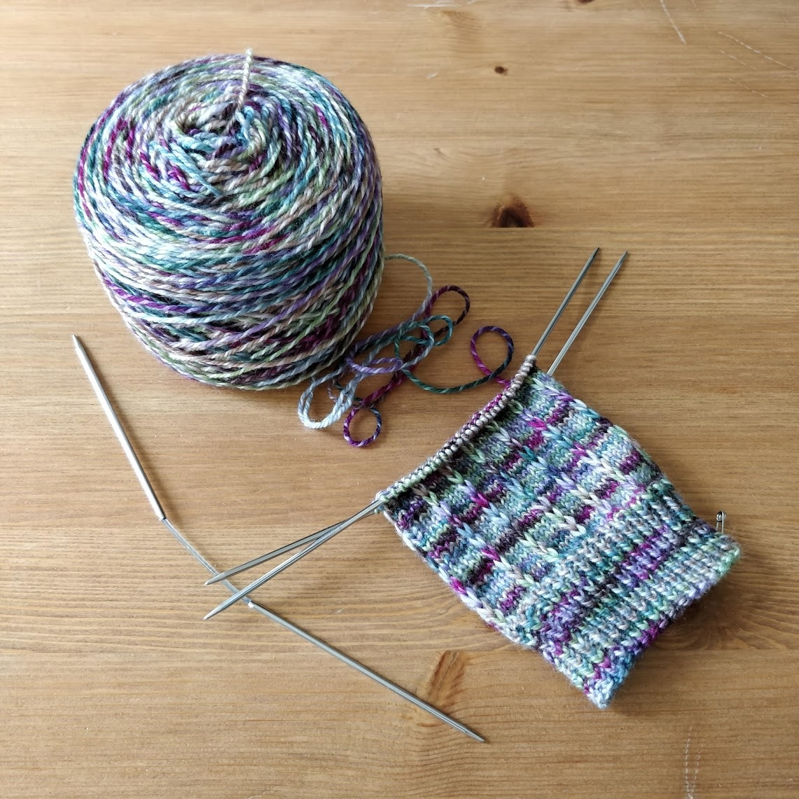 The start of a knitted sock leg on Flexi-Flip needles,with columns of slipped stitches on a stockinette background