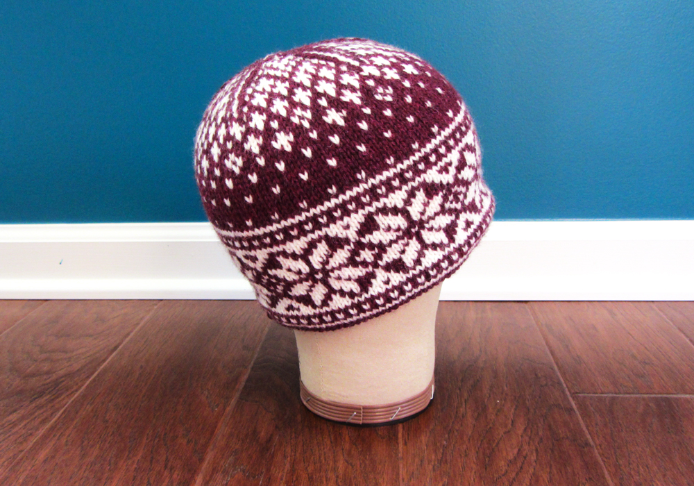 The Sneaux Zone Hat, in burgundy and white stranded colourwork, is displayed on a hat form.