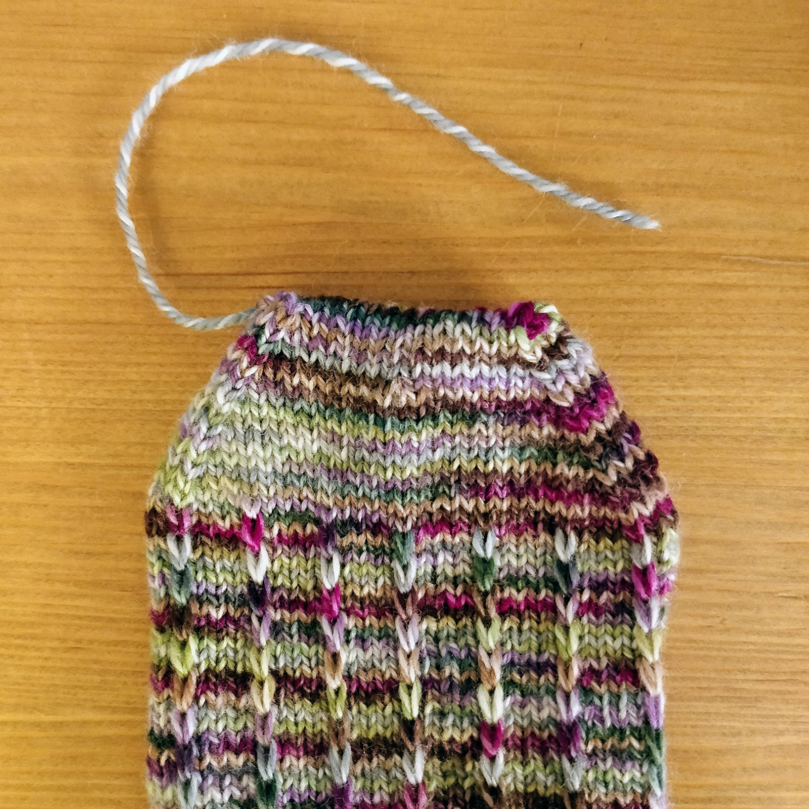 The finished toe of a new sock, with only a few inches of yarn dangling from one corner.