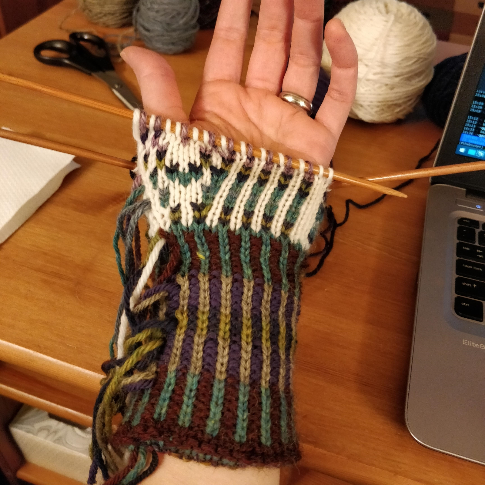 The palm side of a colourwork mitten in progress, showing the start of a thumb gusset.