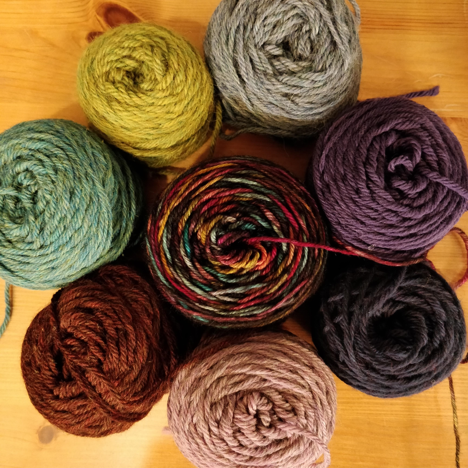 A collection of small balls of yarn in shades of greens, purples and blues.