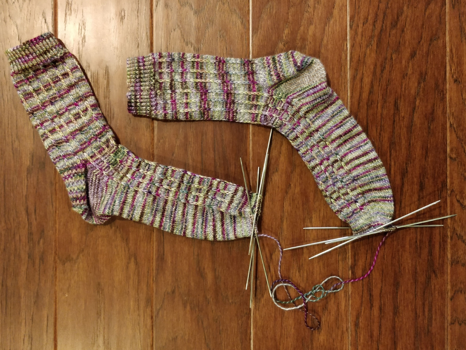Two almost-finished socks, with about thirty inches of yarn connecting both of them.
