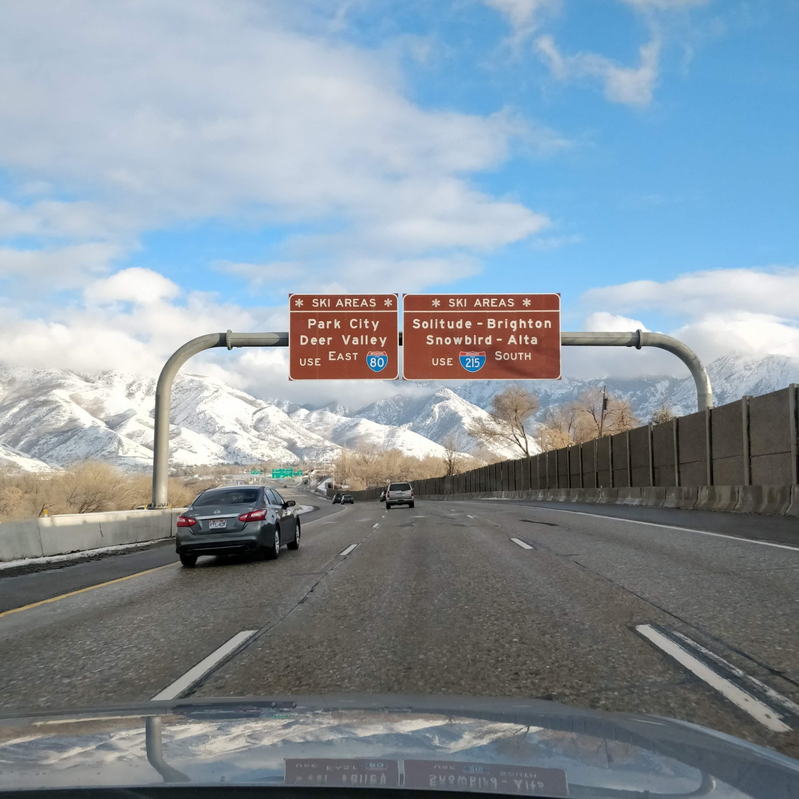 The highway to Utah ski resorts, with directional signs to each one, and tall mountains in the background
