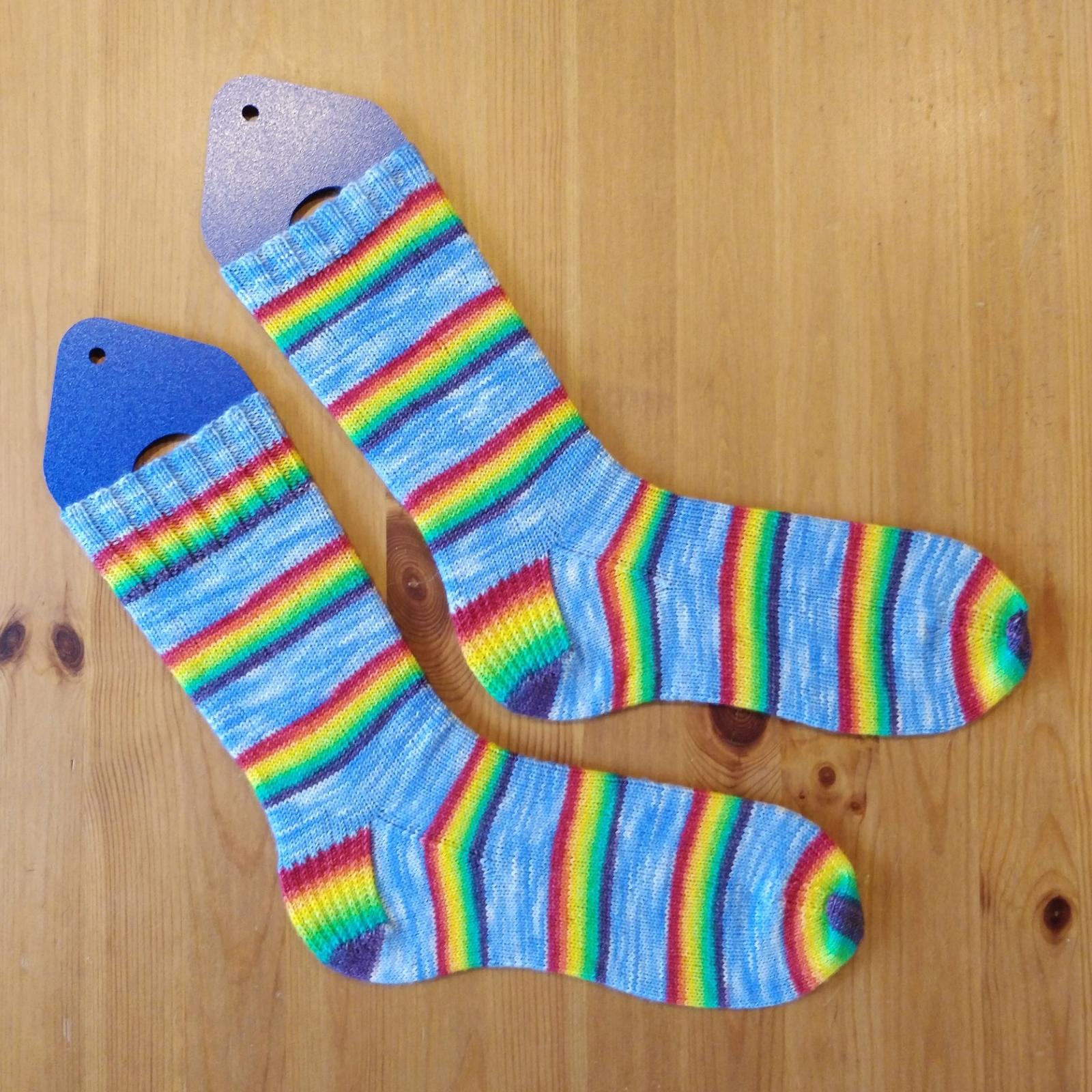 A pair of light blue socks with rainbow stripes.