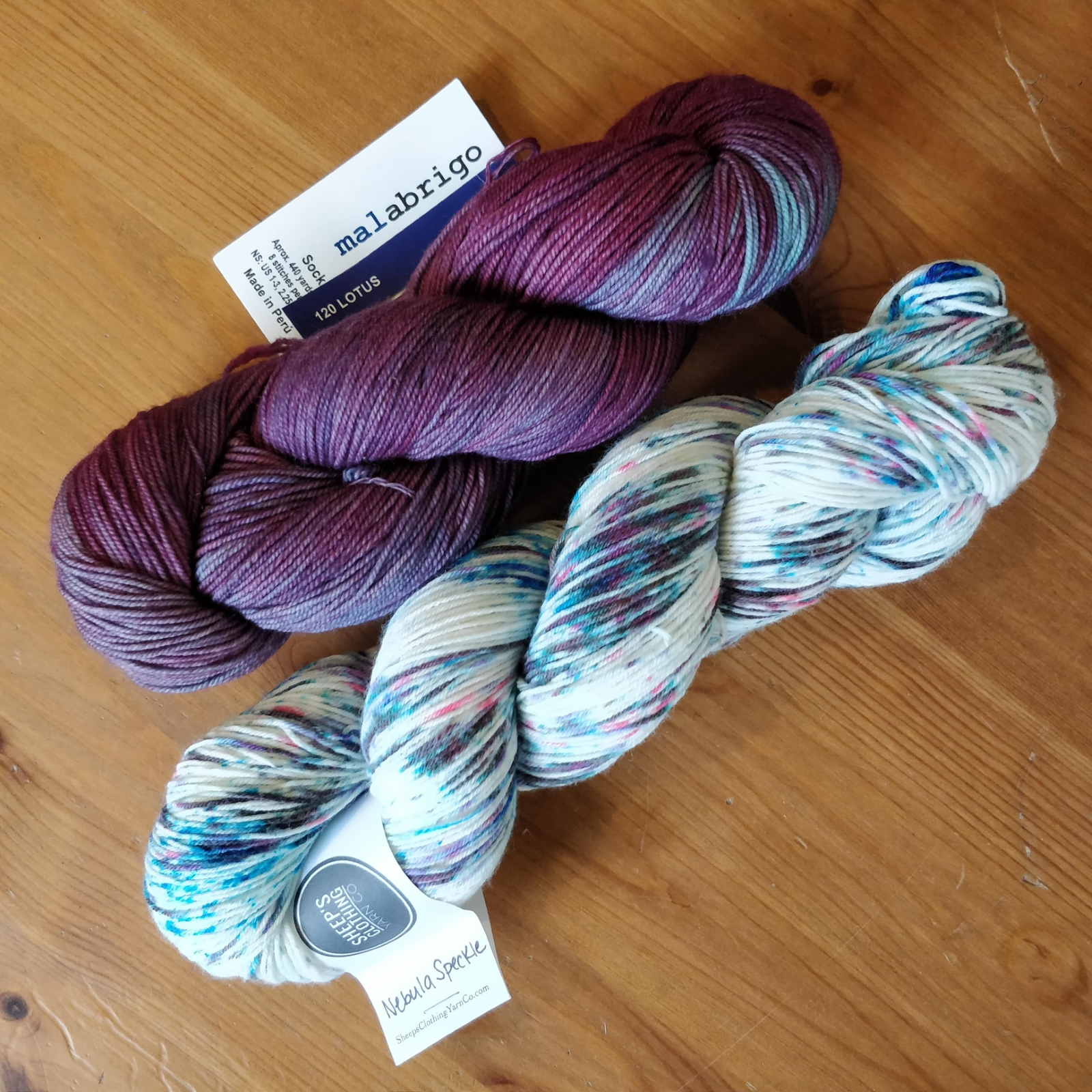 Two skeins of sock yarn - one dark purple with a tinge of cyan, the other mostly white with purple/blue/pink speckles